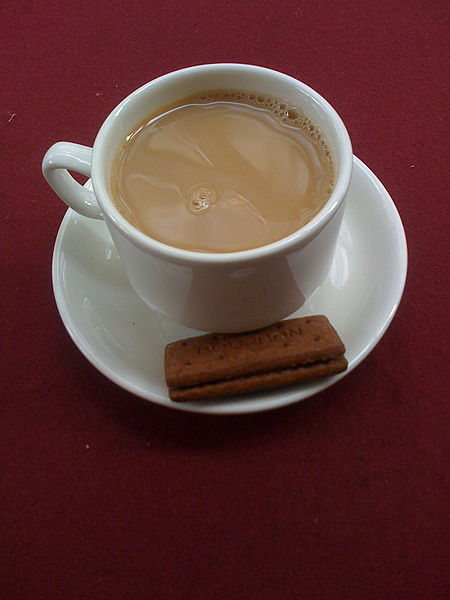 A cup of tea with milk, in a white cup on a white saucer. The saucer also holds two think rectangular cookies. It all sits on a maroon cloth.