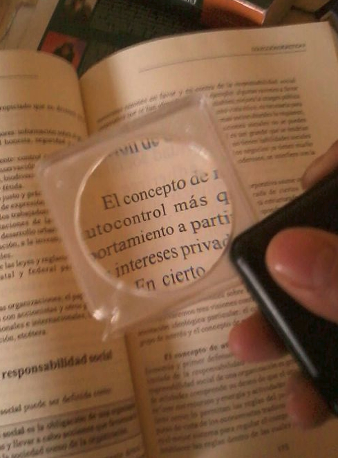 A book being viewed through a magnifying glass.